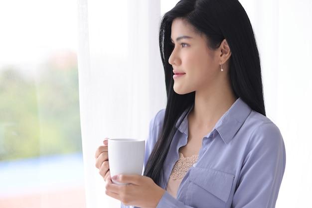 柔らかなカーテンで外を見ながらリラックスして簡単なジェスチャーで白いセラミックコーヒーカップを保持している若くて美しいアジアの女性。朝の幸せのためのアイデア。