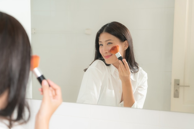 젊고 아름다운 아시아 여자는 거울을보고 자신을 만들어