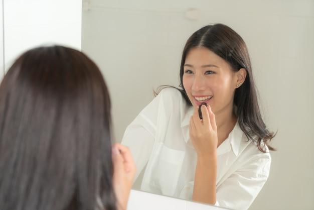 若くて美しいアジアの女性は鏡を見て自分自身を構成します