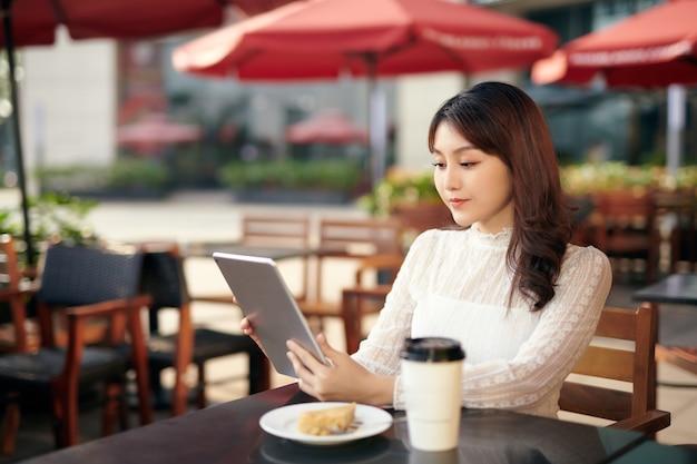 都会のアウトドア コーヒー ショップに座ってタブレット pc を使用する若くて美しいアジアの女性