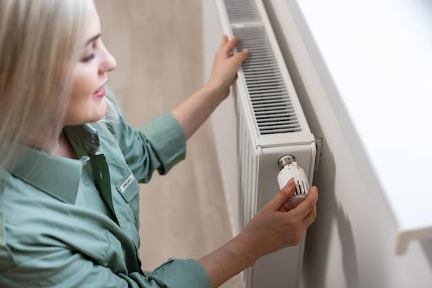 Молодая и красивая белокурая женщина, касаясь радиатора. концепция отопительного сезона.