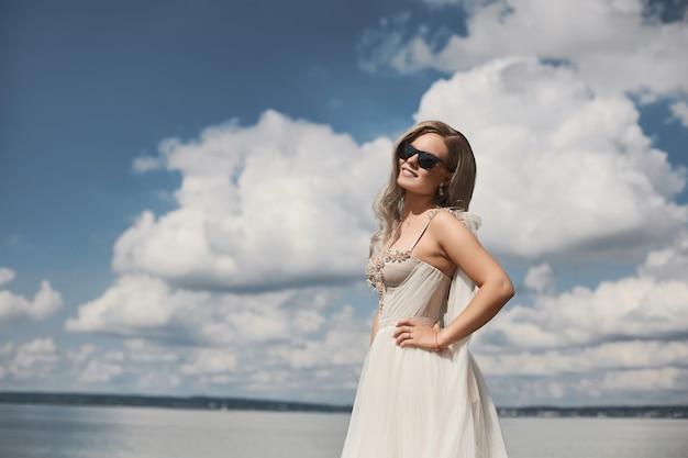 夏の日の屋外でスタイリッシュなドレスを着た若くて美しい金髪モデルの女性