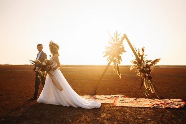 Молодая и красивая невеста и жених наслаждаются друг другом. день свадьбы в стиле бохо.