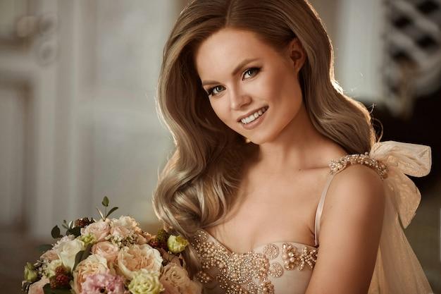 Молодая и красивая невеста, счастливая блондинка модель девушка с нежным макияжем и свадебной прической в стильном платье с букетом цветов в руках