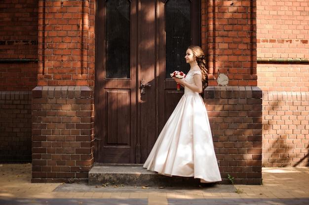빈티지 건물의 나무 문 근처에 서있는 하얀 웨딩 드레스의 젊고 아름다운 신부