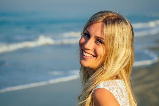 긴 금발 머리를 가진 젊고 아름다운 신부는 아름답게 웃고 아름다운 흰색 긴 웨딩 드레스를 입고 바다 위를 걷고 있습니다. 행복한 신부는 바다 해변에서 결혼식을 올렸다