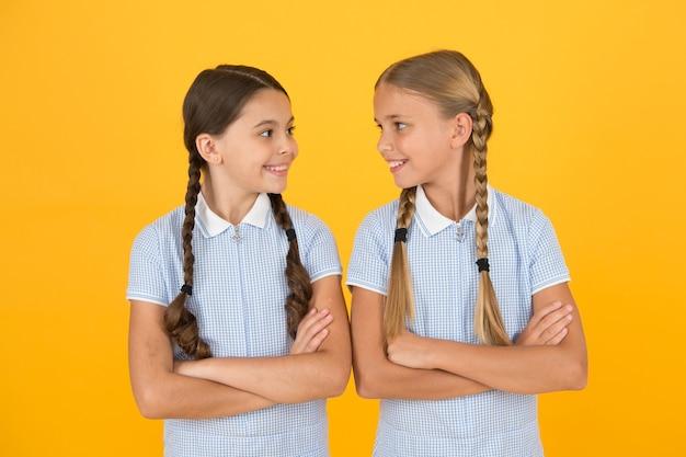 젊고 아름다운. 갈색 머리와 금발 머리. 자매결연 개념. 가장 친한 친구. 빈티지 스타일. 복고 제복을 입은 작은 소녀. 오래된 학교. 학교로 돌아가다. 땋은 머리와 함께 행복 한 아름다움입니다. 행복한 어린 시절.