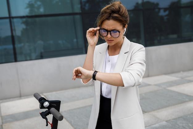 若くて美しい実業家が街で電動スクーターに乗る