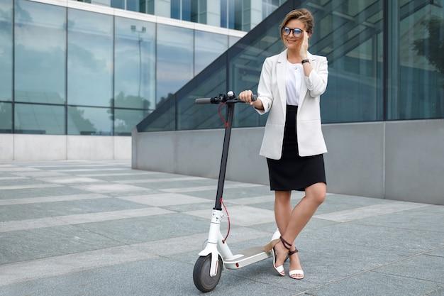 젊고 아름다운 사업가 도시에서 전기 스쿠터를 타고
