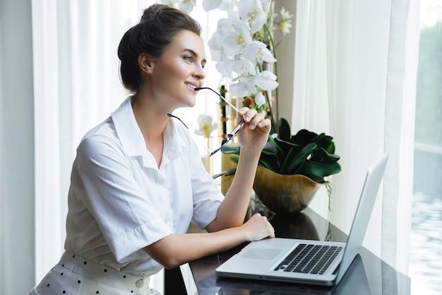 白いシャツを着ている若くて美しい女性実業家