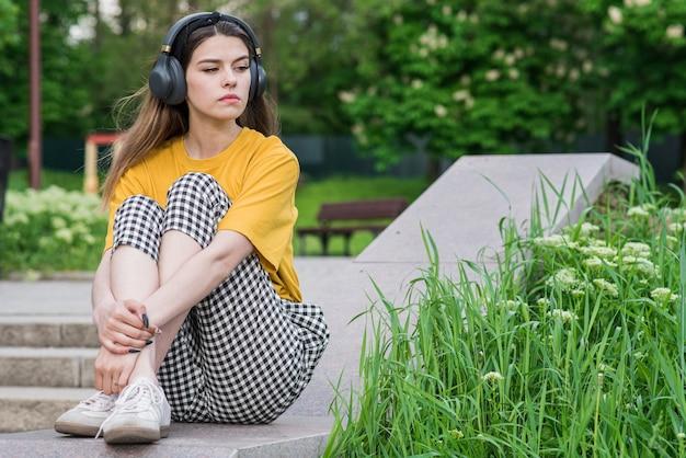 若くて美しい白人の女の子は悲しい。ヘッドフォンで屋外に座って音楽を聴く