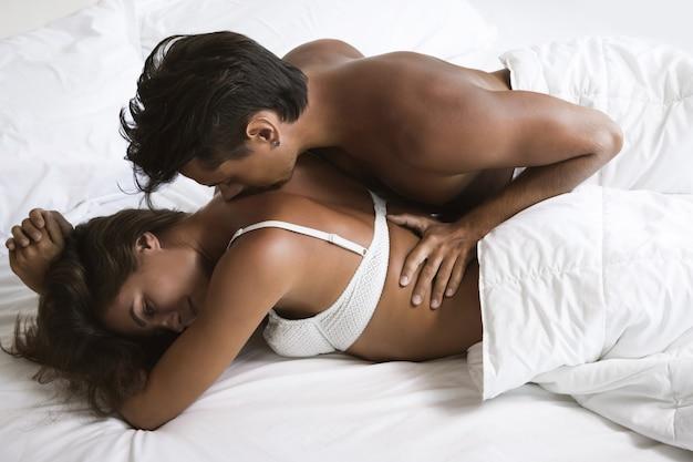 젊고 아름다운 부부는 아침에 침대에 누워있다
