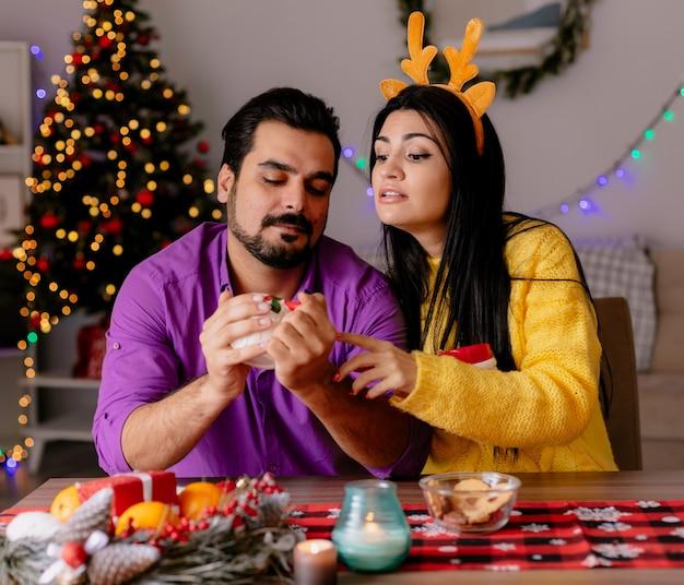 젊고 아름다운 부부 남자와 여자는 벽에 크리스마스 트리와 함께 크리스마스 장식 방에 사랑에 행복 차 컵 테이블에 앉아