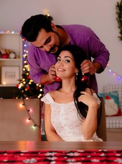バックグラウンドでクリスマスツリーとクリスマスの装飾が施された部屋で楽しんで彼女のガールフレンドの耳にクリスマスボールをぶら下げて若くて美しいカップルの男