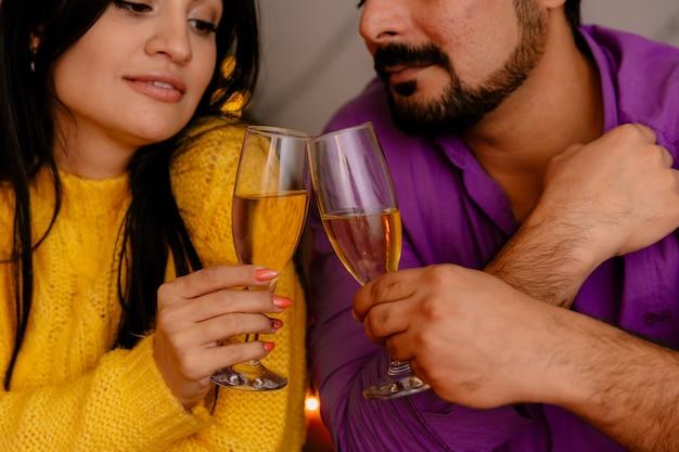 Молодая и красивая пара, сидящая за столом с бокалами шампанского, счастливая в любви, празднует рождество вместе в рождественской украшенной комнате с елкой на заднем плане