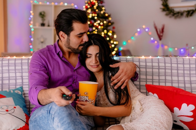 Молодая и красивая пара, сидящая на диване, мужчина и женщина с ведром попкорна, вместе смотрят телевизор, счастливы в любви в украшенной комнате с рождественской елкой на заднем плане