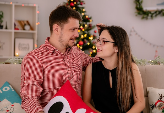 Молодая и красивая пара, сидящая на диване, счастливая в любви, глядя друг на друга в рождественской комнате с елкой на заднем плане
