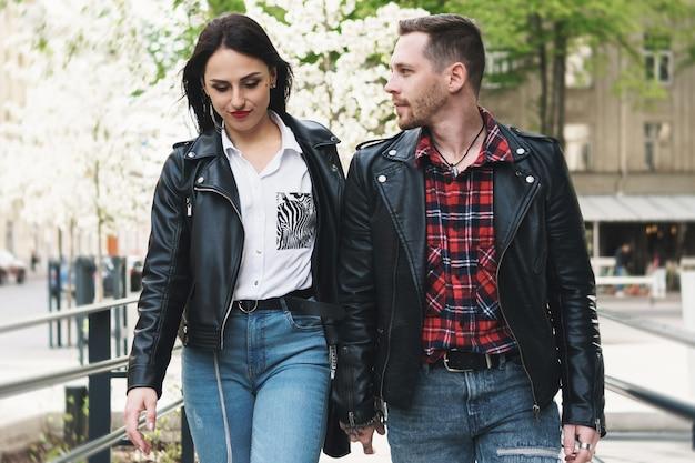 거리에서 데이트하는 동안 가죽 자켓을 입고 젊고 아름다운 커플