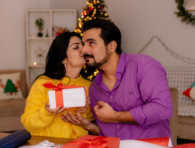 Молодая и красивая пара женщина принимает подарок и целует своего парня в рождественской комнате с елкой на заднем плане