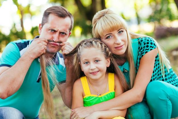 公園の若くて美しい家族。母、父、娘