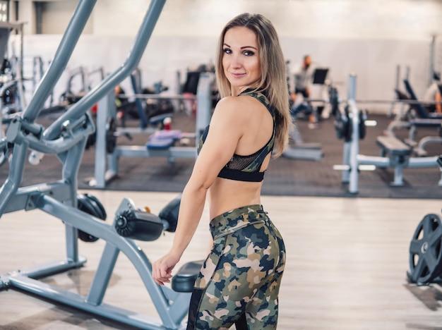 Молодая и красивая фитнес-тренер смотрит в камеру в тренажерном зале. тренер позирует