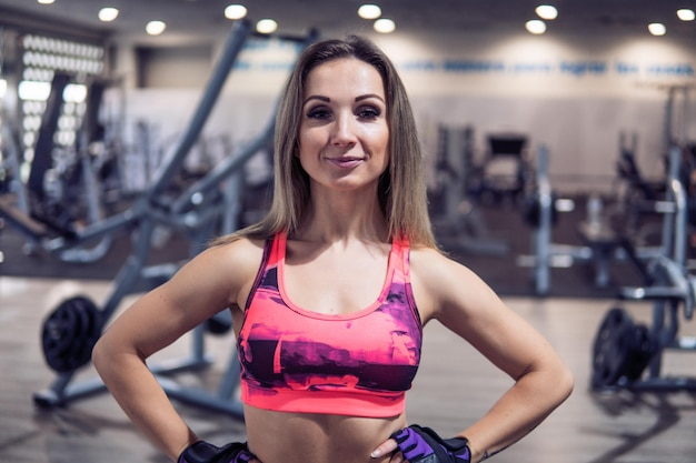 Молодые и красивые фитнес-тренер позирует перед камерой в тренажерном зале. тренерская сила