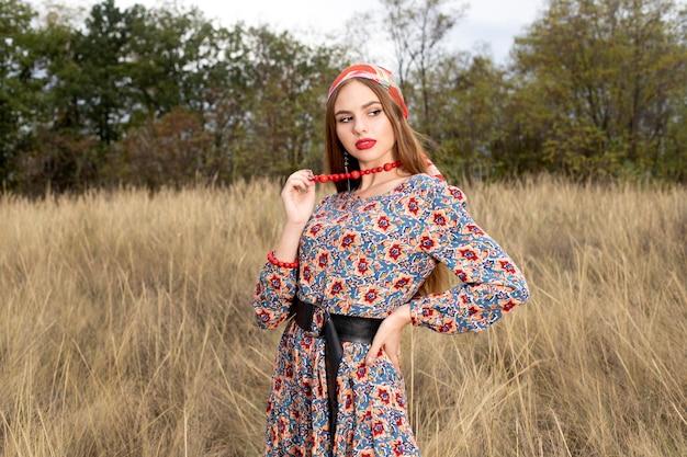 自然の中でポーズをとるドレスとジュエリーの若くて美しい女の子モデル