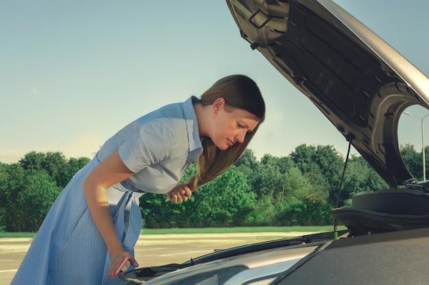 Молодая и красивая девушка возле разбитой машины с открытым капотом. проблемы с машиной, не заводится, не работает.