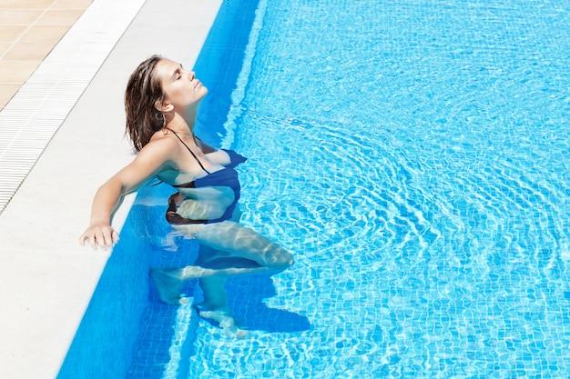若くて美しい女の子がプールでリラックスします。夏の外。