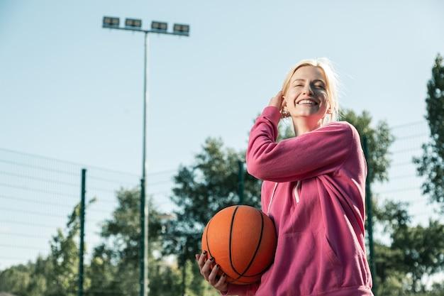 若くて美しい。バスケットボールのボールで立っている間彼女の髪に触れるうれしそうな幸せな女性