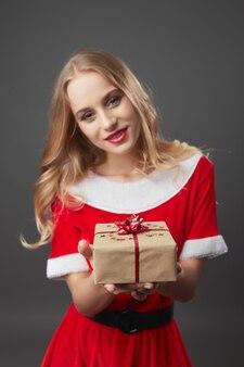 Молодая и красивая миссис клаус в красном халате и белых перчатках держит в руках рождественский подарок на сером фоне. .