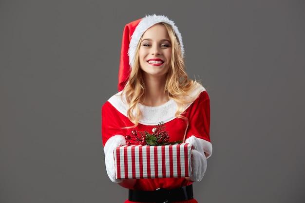 Молодая и красивая миссис клаус, одетая в красный халат, шляпу санты и белые перчатки, держит в руках рождественский подарок на сером фоне. .