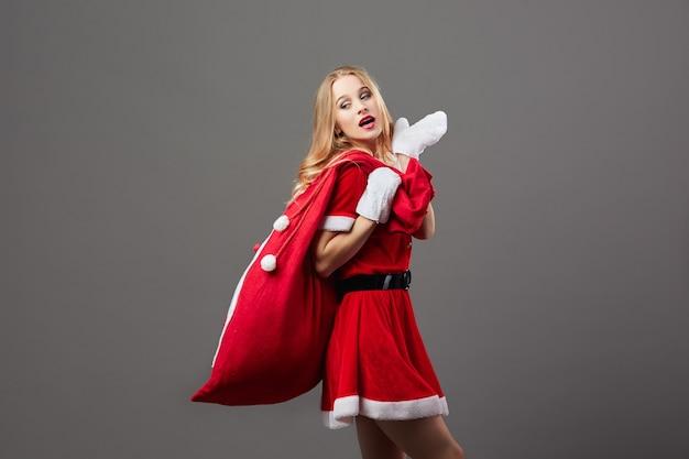 Молодая и красивая госпожа санта-клаус, одетая в красный халат и белые перчатки, держит на спине сумку с рождественскими подарками. .
