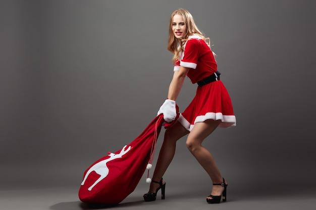 Молодая и красивая госпожа санта-клаус в красном халате и белых перчатках тянет сумку с рождественскими подарками по полу на сером фоне. .