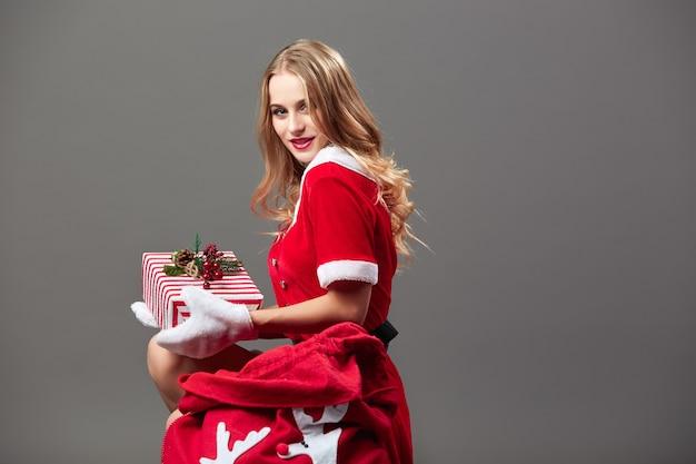 Молодая и красивая госпожа санта-клаус, одетая в красный халат и белые перчатки, сидит возле сумки с рождественскими подарками и держит подарок в руках на сером фоне. .