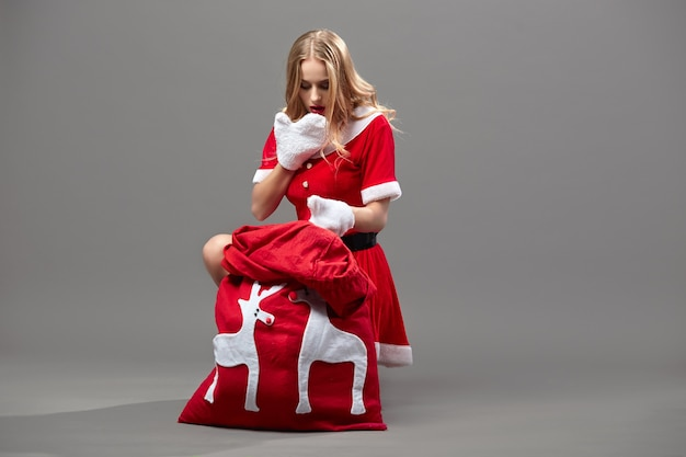 Молодая и красивая госпожа санта-клаус в красном халате и белых перчатках сидит возле мешка с рождественскими подарками и выглядит в нем удивленным на сером фоне. .