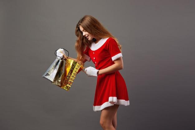 젊고 아름다운 산타클로스는 빨간 가운과 흰 장갑을 끼고 선글라스를 끼고 선물이 든 가방을 들고 회색 배경에 있는 가방을 들여다봅니다.