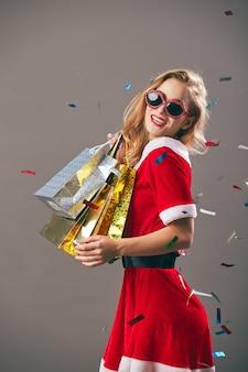 Молодая и красивая миссис санта-клаус в солнечных очках, одетых в красный халат и белые перчатки, держит сумки с подарками и улыбается на сером фоне с конфетти. .