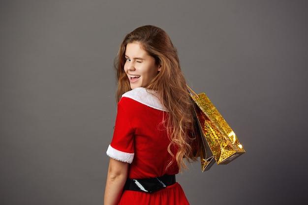 젊고 아름다운 산타클로스는 빨간 가운과 흰 장갑을 끼고 선글라스를 끼고 회색 배경에 선물과 윙크가 든 가방을 들고 있습니다.