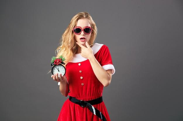 Молодая и красивая миссис санта-клаус в солнечных очках, в красном халате и белых перчатках держит часы, которые показывают без пяти двенадцать. канун рождества .
