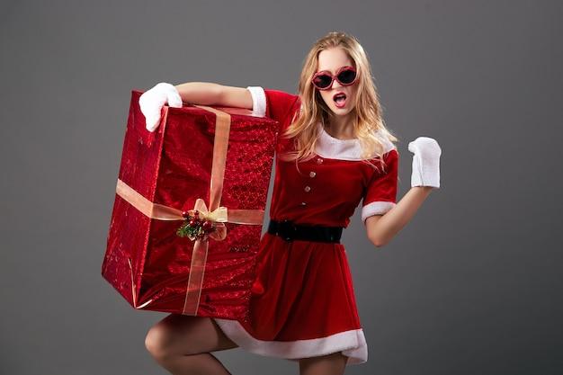 Молодая и красивая миссис санта-клаус в солнечных очках, одетом в красный халат, белые перчатки и высокие каблуки держит огромный рождественский подарок на сером фоне. .