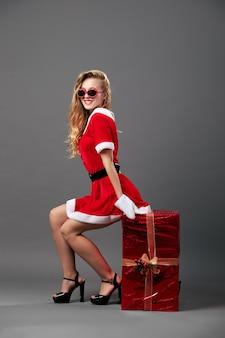 Молодая и красивая миссис санта-клаус в солнечных очках, одетом в красный халат, белые перчатки и высокие каблуки сидит на огромном рождественском подарке на сером фоне. .