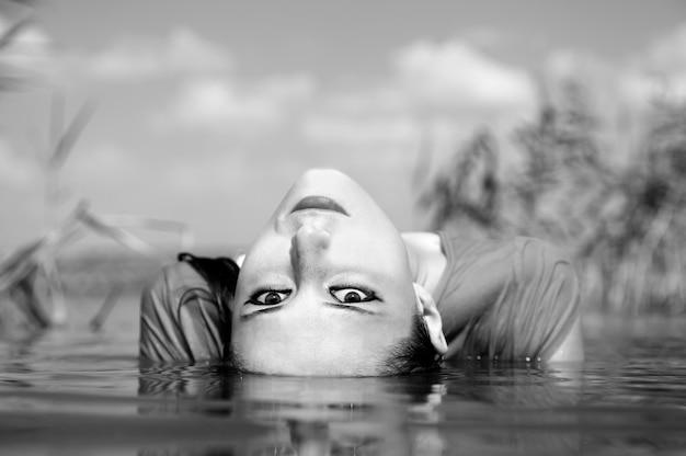 川の若くて美しい野蛮な女の子。騒々しい白黒スタイルの写真。