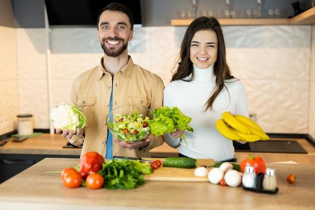 Молодые и красивые вегетарианские пары улыбаются на кухне во время приготовления пищи.