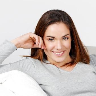 Молодая и красивая женщина одна на диване