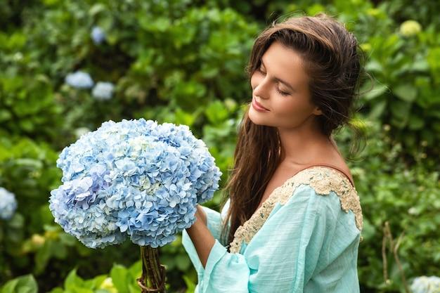 Молодая и красивая женщина-флорист собирает цветы гортензии в поле