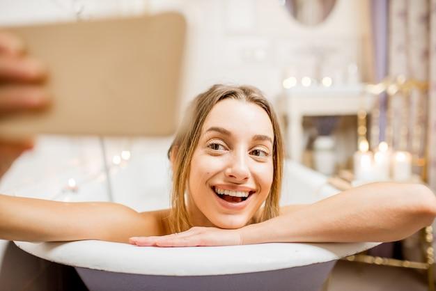 屋内のレトロなお風呂に横たわっている携帯電話で自分撮り写真を作る若くて美しい女性