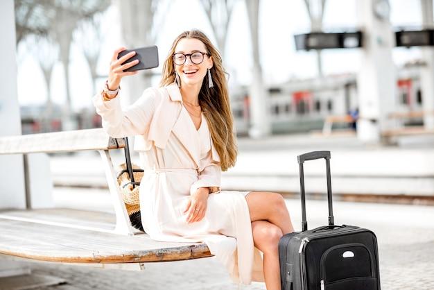 Молодая и красивая женщина делает селфи портрет, сидя с багажом на вокзале