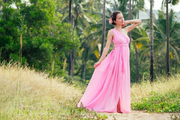 ヤシの木を背景にエレガントなピンクの長くシックな豪華なドレスでポーズをとる若くて美しい女性。トロピカルリゾートでのシックな休暇のコンセプト