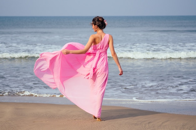 Молодая и красивая женщина позирует в элегантном розовом длинном шикарном роскошном платье на пляже с волнами. концепция шикарного отдыха на тропическом курорте.